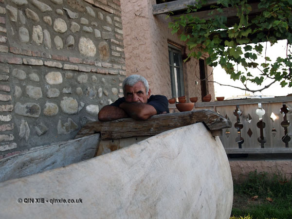 Man by grape crusher in Georgia