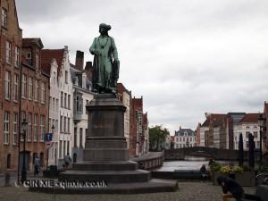 Statue by river, Bruges, Belgium